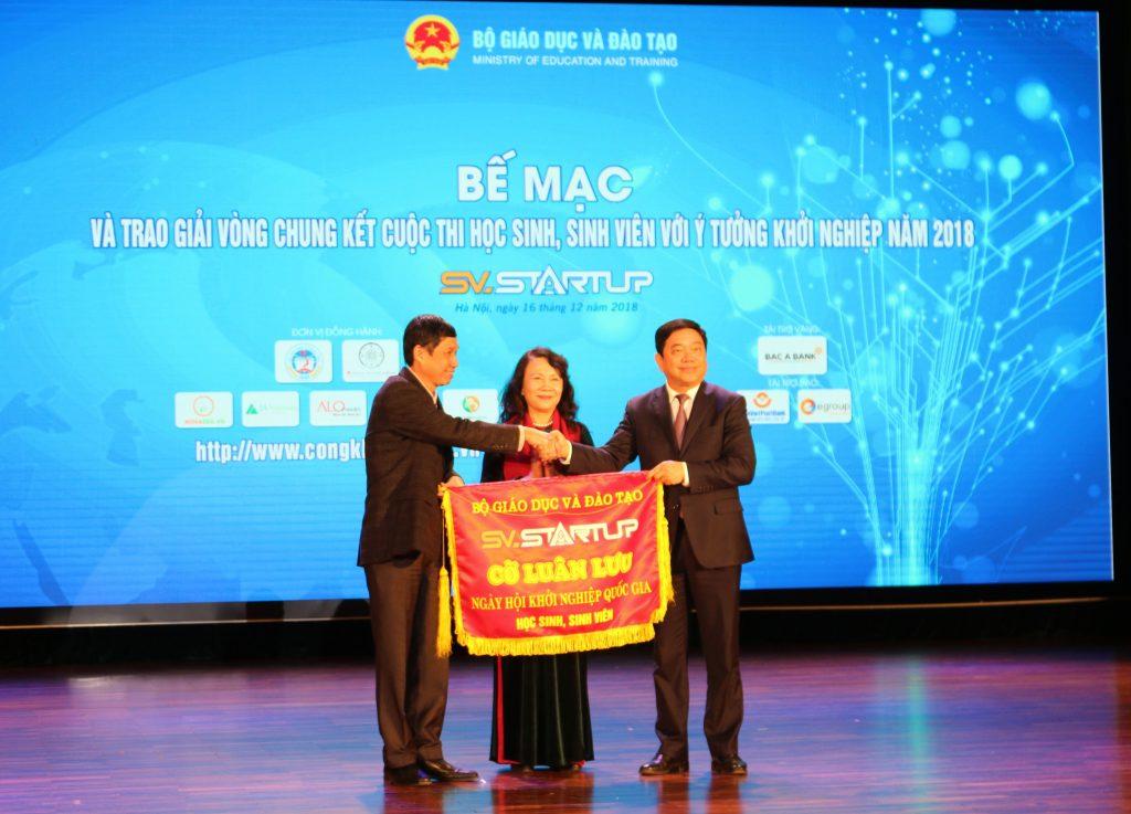 Đại diện trường Đại học Kinh tế Quốc dân trao cờ luân lưu cho đại diện trường Đại học Bách khoa Hà Nội dưới sự chứng kiến của Thứ trưởng Bộ Giáo dục và Đào tạo Nguyễn Thị Nghĩa.